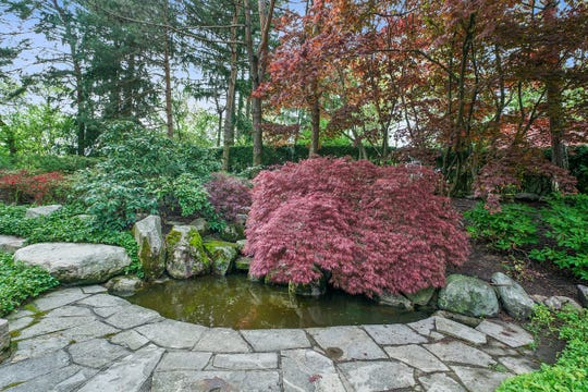 Another Japanese Zen garden in the rear yard has a small pond, a weeping Japanese red maple and stones used as sculpture.