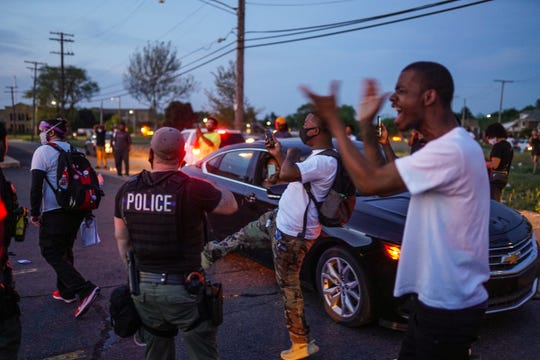 A number of the residents from a nearby neighborhood near Gratiot and East Outer Drive in Detroit cheer as the police usher out one of the protesters on Tuesday, June 2, 2020. In violation of the city-imposed curfew, a large group of protesters encountered a large contingent of Detroit police officers who quickly moved in and arrested many in the group and dispersed the rest. Many of the neighborhood residents weren't happy the standoff between protesters and police happened in their area.