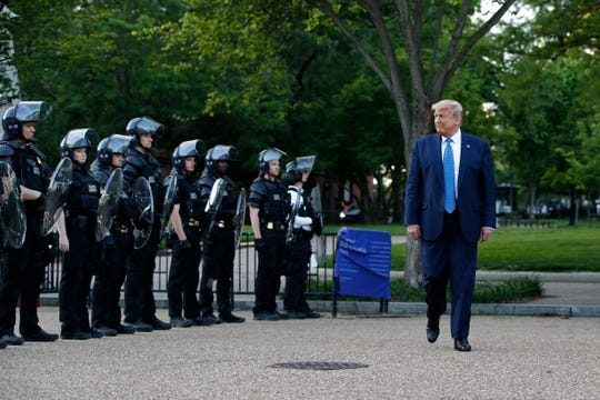 President Donald Trump walks past police in Lafayette Park after visiting outside St. John's Church across from the White House Monday, June 1, 2020, in Washington.