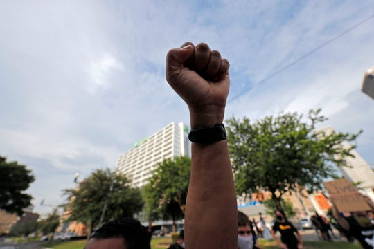 A demonstrator raises a fist in the air during a peaceful march Tuesday in downtown New Orleans. They were protesting over the death of George Floyd, a black man who was in police custody in Minneapolis. Floyd died after being restrained by Minneapolis police officers on Memorial Day.