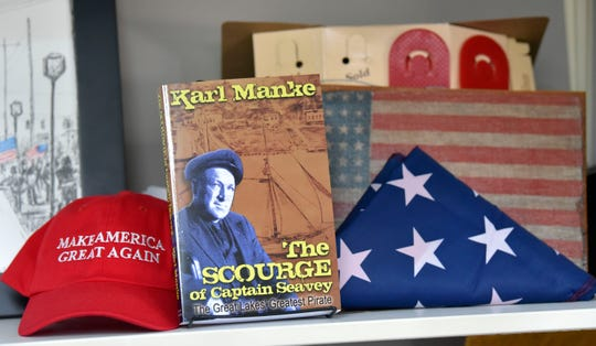 A Make America Great Again hat, a folded U.S. flag and 48-star U.S. flag are gifts to barber Karl Manke that he displays on a shelf next to a book he authored called, 'The Scourge of Captain Seavey The Great Lakes Greatest Pirate.'