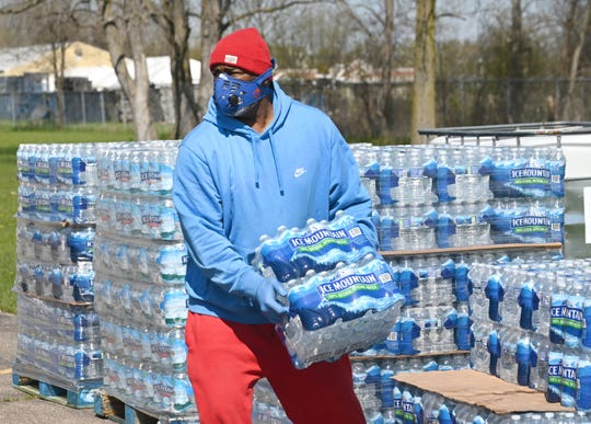 Volunteer Arthur Woodson, R.L. Community Outreach Center, carries cases of water at the Greater Holy Temple as the mobile food pantry distribution loaded vehicles for resident in need in Flint.