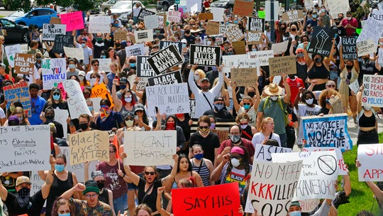 In this May 30, 2020 file photo protesters, some wearing masks, some not, demonstrate in Salt Lake City.
