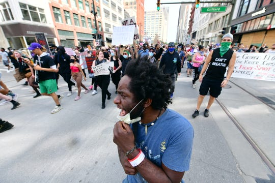 """Tristan Taylor shouts """"say his name"""" as he and other protestors march north on Woodward Avenue in Detroit, Wednesday, June 3, 2020."""