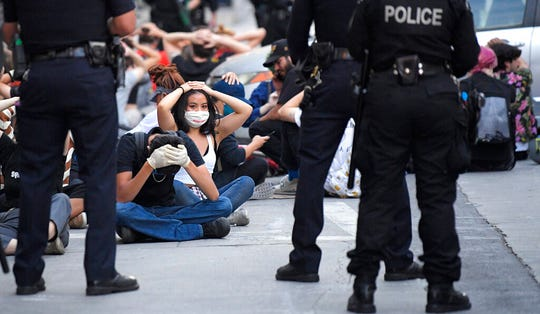 Demonstrators put their hands on their heads before being taken into custody after the city's curfew went into effect Tuesday, June 2, 2020, in Los Angeles during a protest over the death of George Floyd.