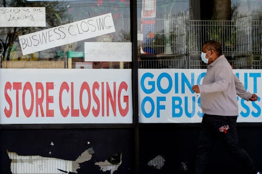 In this May 21, 2020 file photo, a man looks at signs of a closed store due to COVID-19 in Niles, Ill.