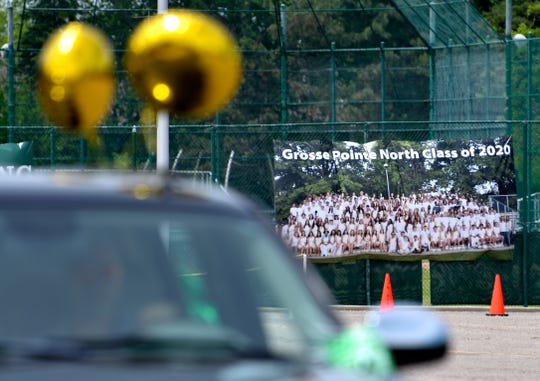Students drive past a Grosse Pointe North Class of 2020 group shot.