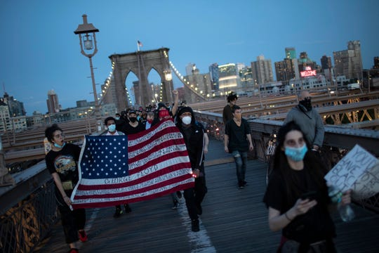 Protesters march across the Brooklyn Bridge as part of a solidarity rally calling for justice over the death of George Floyd Monday in the Brooklyn borough of New York. Floyd died after being restrained by Minneapolis police officers on May 25.