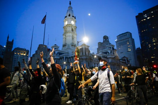 Demonstrators march Tuesday, June 2, 2020, near City Hall in Philadelphia, during a protest over the death of George Floyd.