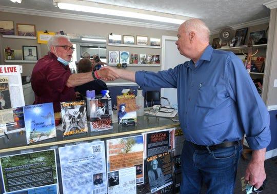U.S. Army Vietnam veteran Dennis Roper, right, of Northville, shakes hands with barber Karl Manke.