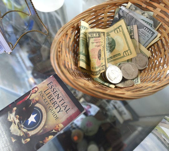 Older Kennedy half dollars are part of a tip from a client as they money basket rests near 'The Patriot's Essential Liberty Pocket Guide.' The guide is 'devoted to the restoration of rule of law as enshrined in our Constitution.'