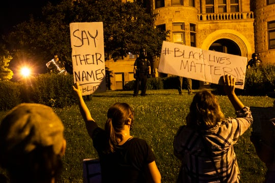 """Protesters hold up signs, """"Say their names,"""" and """"#BlackLivesMatter"""" as law enforcement officers wear riot gear outside the Johnson County Courthouse during a protest, Tuesday, June 2, 2020, in Iowa City, Iowa."""