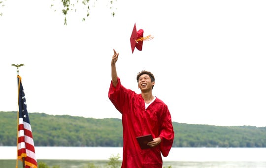 Terry Paw, an graduating Ithaca High School senior, throws his cap in the air after receiving his diploma during a socially distanced graduation stage walk at Stewart Park. Over the course of several days, the seniors were videotaped and photographed in their caps and gowns as they received their diplomas. June 2, 2020.