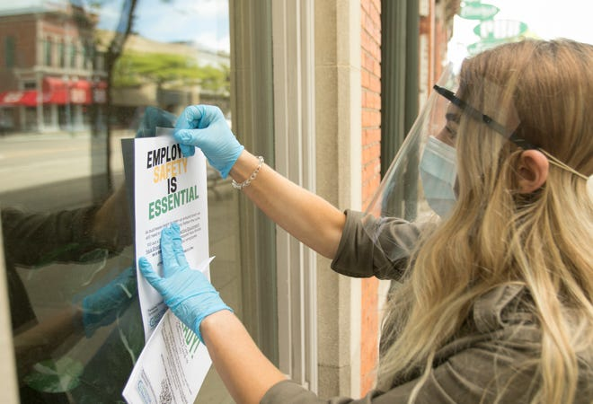 Katie Griffen, a Hartland High School graduate living in Howell, posts flyers throughout downtown Howell Friday, May 29, 2020 to put out word that she has free face shields available.