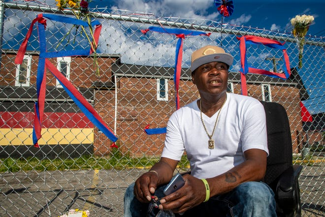 Marvin McAtee sits along the fence at 26th and Broadway in Louisville where his uncle, YaYa's BBQ business owner David McAtee, was shot and killed in his business during a confrontation with police and the national guard. June 2, 2020