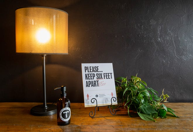 A hand sanitizer and a social distancing notice are seen on a table at the entrance of the Iron Horse Hotel on Wednesday. After closing for more than two months because of the COVID-19 pandemic, the Iron Horse Hotel reopened on Monday.