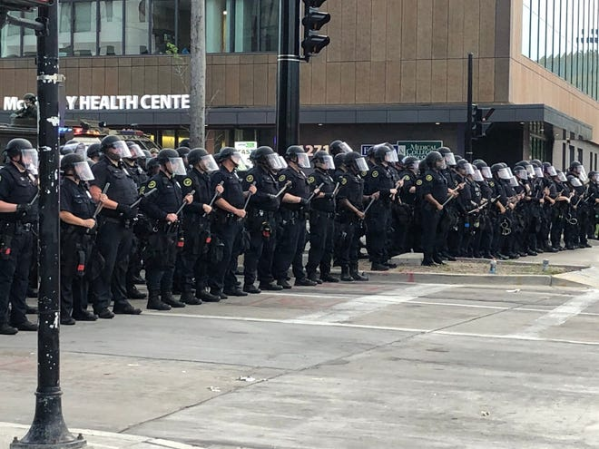 Police stand along 6th Street in Milwaukee on Tuesday, June 2, 2020.