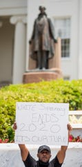 Tavorius Dennis holds his sign as the statue of Jefferson Davis stands in the background during a Black Lives Matter protest march held at the Alabama State Capitol Building in Montgomery, Ala., on Wednesday June 3, 2020.