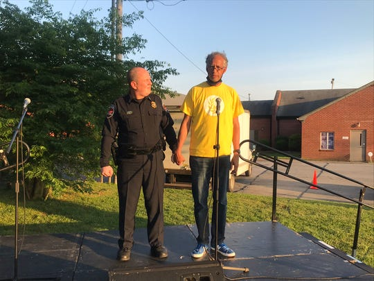 The Rev. Vincent Windrow, right, pastor of Olive Branch Church in Murfreesboro, holds the hand of Murfreesboro Police Chief Michael Bowen as the two men pray at the end of a community forum held outside the church Tuesday night.