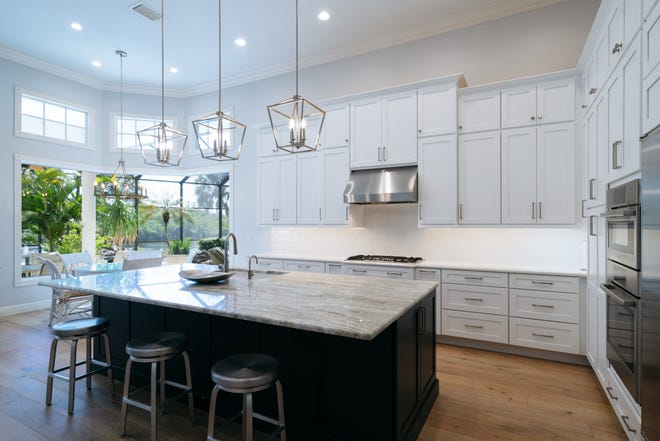 A transitional-inspired style makeover provides a transformed kitchen and family room open concept space in the remodel of a luxury home kitchen in Bonita Bay by Green Mountain Builders.