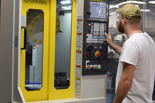 A C-TEC adult education student programming a robodrill in the General & CNC machining program, a program that focuses on foundation and automation.