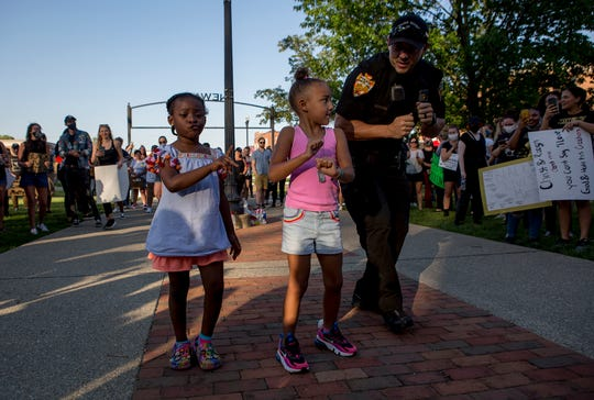 Newark Officer Steven Carles dances with Zada Anderson and Tahlia Watson Tuesday at a Black Lives Matters protest in downtown Newark. The protest was peaceful with Newark police and the Licking County Sheriffs chatting with the crowds. A group with assault rifles called Ohio Patriots were present, but were there to protect the protesters in case activators showed up.