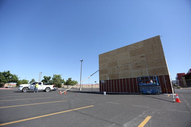 Crews construct a movie screen on the side of three shipping containers stacked upon each other in the parking lot of Telshor 12 in Las Cruces on Wednesday, June 3, 2020. The drive-in theater will begin Friday.