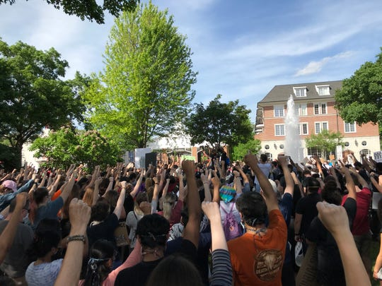 Protesters take a moment of silence with their fists up to honor the death of George Floyd.