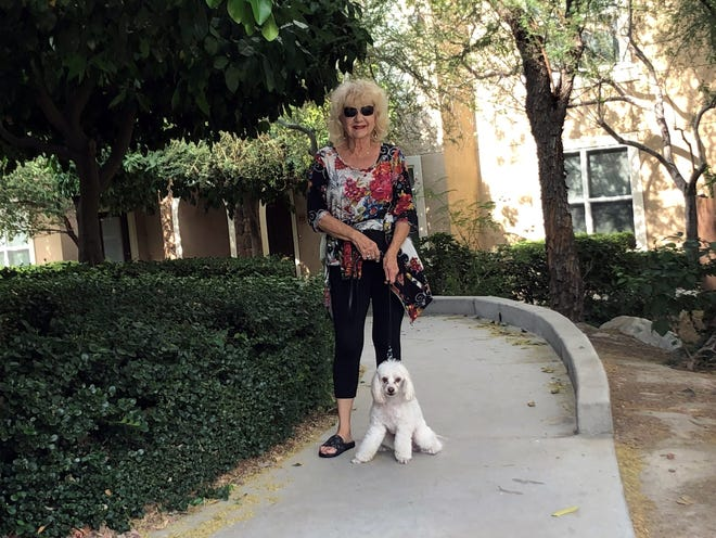 For exercise and to keep herself busy, Cheri Steinker walks her miniature poodle, Blessing.