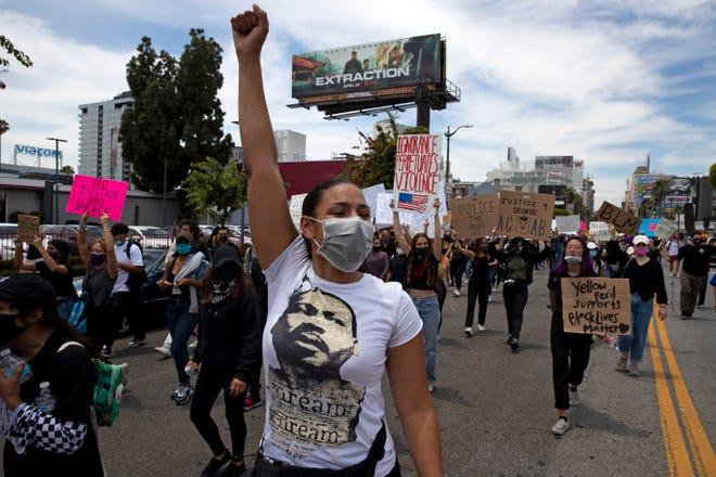 Una mujer, que viste una camiseta de Martin Luther King Jr., marcha por la calle pidiendo justicia por la muerte de George Floyd.