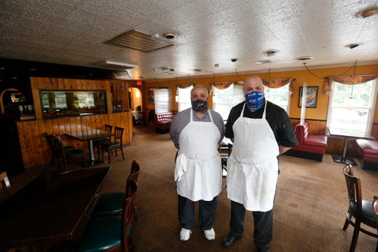 From left, brothers John and Luigi Coppola inside the dining room at Coppola's Restaurant in Hyde Park on June 3, 2020. In preparation for re-opening amid the coronavirus pandemic they have removed most of the tables and added barriers between booths.