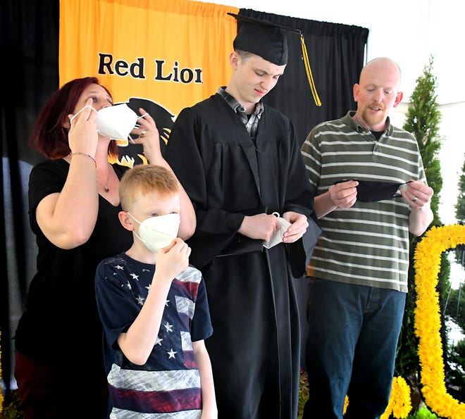 "The Schussler family, from left, mother Sara; Lukus, 9; graduate Nathan, and father Phil prepare for a ""masked"" portrait during the Class of 2020 Graduate Photo Opportunity at Red Lion High School Wednesday, June 3, 2020. In addition to the taking of official graduation photos, students returned school property and received gifts along with their diplomas. Bill Kalina photo"