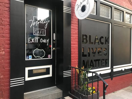 Molly Fisher, owner of Molly's Courtyard Cafe on West Philadelphia Street in York, painted her front window in solidarity with protesters.