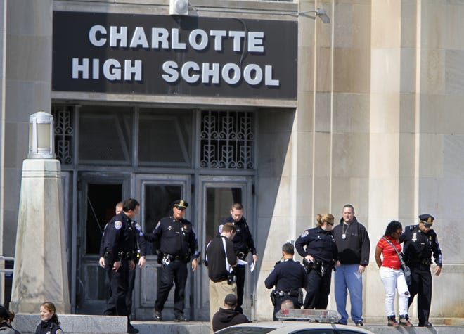 In this file photo Rochester police officers exit Charlotte High School after a fight on the campus in 2010.