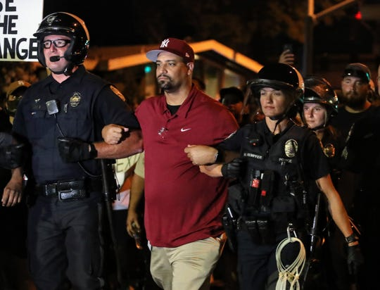 Pastor Curley Wilson marches with two police officers on Tuesday, June 2, 2020, during a protest in downtown Redding. Officers and protesters linked arms at the end of the demonstration, one of two held that night to protest George Floyd's death at the hands of Minneapolis police.