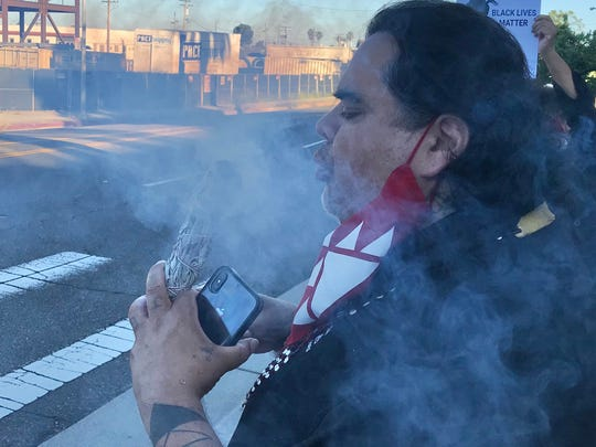 Jack Potter Jr., chairman of the Redding Rancheria, burns sage smoke to bring a good spirit to the George Floyd protest on Tuesday, June 2, 2020 in downtown Redding.