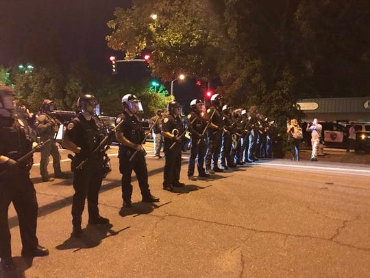 Redding police hold batons and block off Court Street amid protests over George Floyd's death.