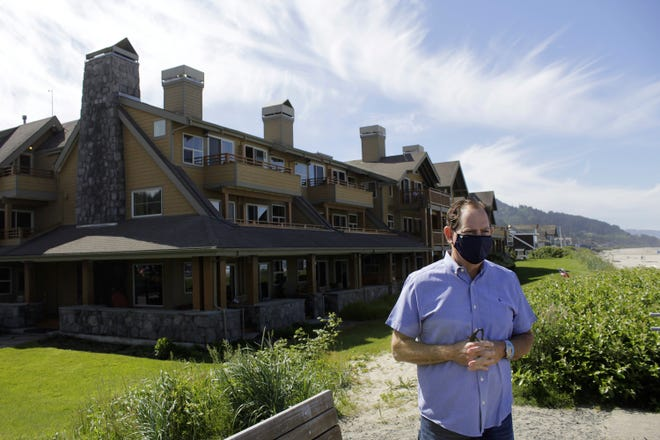 In this Thursday, May 28, 2020, photo, Patrick Nofield, whose company, Escape Lodging, owns and operates four hotels in Cannon Beach, Ore., stands in front of the flagship property, The Ocean Lodge, while wearing a face mask due to the novel coronavirus. With summer looming, Cannon Beach and thousands of other small, tourist-dependent towns nationwide are struggling to balance fears of contagion with their economic survival in what could be a make-or-break summer.