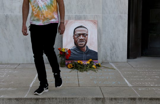 A supporter walks off after placing a flower near a painting of George Floyd during a peaceful rally, celebrating black culture and remembering George Floyd and other victims of police violence, in Salem, Oregon on Tuesday, June 2, 2020.