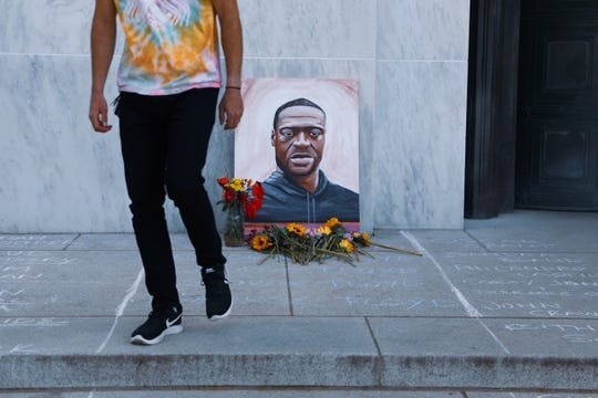Demonstrators placed flowers next to a portrait of George Floyd during an event Tuesday at the Oregon State Capitol