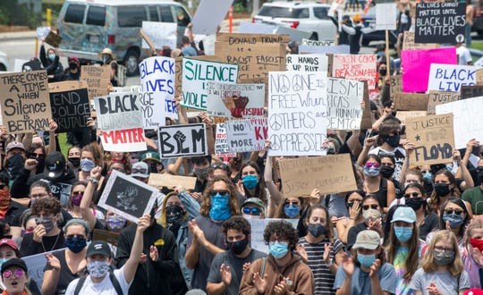 People hold up their signs during a Black Lives Matter protest in Seaside, Calif, on Tuesday, June 2, 2020.