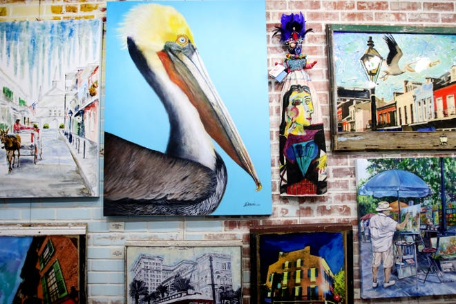 A large brick wall hangs several pieces of art at 318Art&Garden.