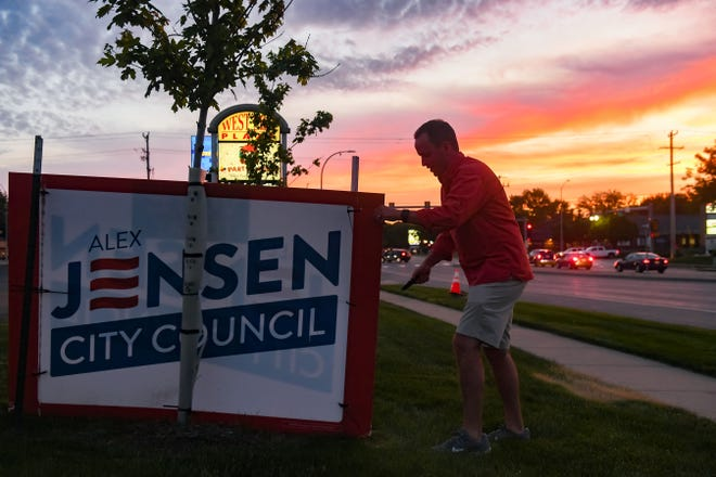 Alex Jensen takes down campaign signs on Tuesday, June 1, in Sioux Falls.