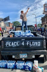 Justin Herberg offers water to people Sunday, May 31, 2020 in Minneapolis.