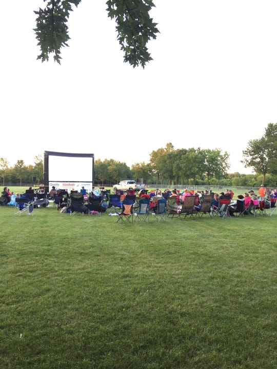 In the past, viewers would bring lawn chairs and blankets to watch movies on the inflatable screen, as these viewers did in 2017. This year, due to COVID-19 distancing requirements, the movie will be a drive-in in the Foley Fieldhouse parking lot.