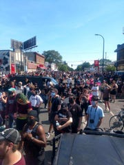 Crowds move around Justin Herberg om Sunday, May 31, 2020 in Minneapolis as he gave out water and other supplies.