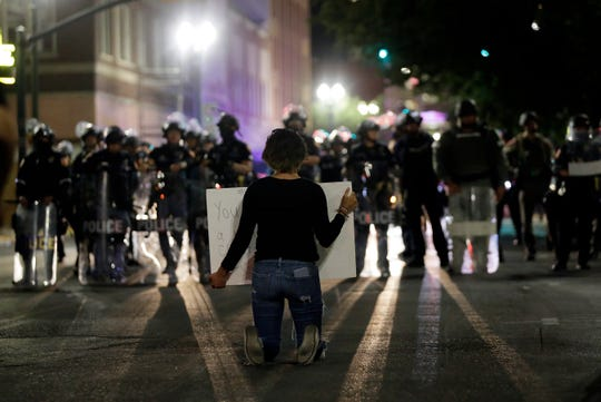 A protesters kneels in front of a police line during the second day of protests Tuesday, June 2, 2020, in El Paso over the death of George Floyd while in the custody of the Minneapolis Police Department. El Pasoans once again took to the streets, this time in Downtown. El Paso police, CBP Field Operations police and state troopers were on scene in full riot gear. The protest was mostly peaceful.