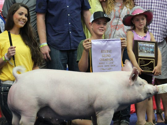 Family members of the reserve grand champion hog smile as bids roll in at the Governor's Blue Ribbon Auction at the Wisconsin State Fair.