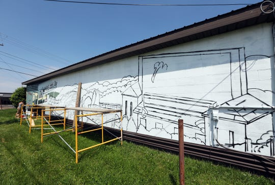 The outline of the former drive-in movie theater is part of a mural being painted by artist Rae Gandolf at Maple Tree Plaza.  The theater used to stand nearby.