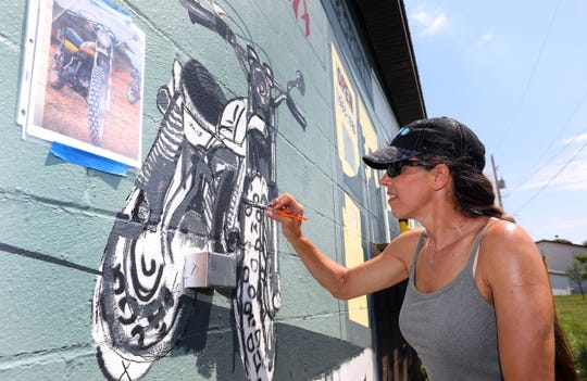 Artist Rae Gandolf paints a motorcycle on a mural at Maple Tree Plaza on Maple Avenue in Zanesville.  The mural will depict some of the businesses that have occupied the plaza since the 1960s.